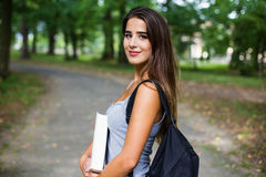 Student girl outside in summer park. Smiling happy Stock Image