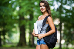 Student girl outside in summer park. Smiling happy Royalty Free Stock Photo