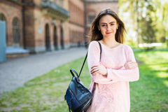 Student girl outside in summer park smiling happy. Caucasian college or university student. Young woman model wearing school bag o. Student girl outside in stock images