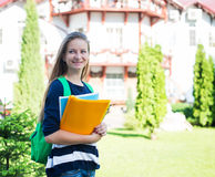 Student girl outside in summer park smiling happy. College or university student young woman with school bag. Stock Photo