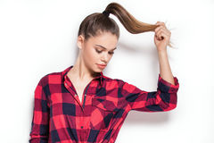 Student girl posing in red checkered shirt. Stock Photo