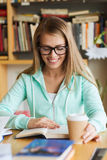 Student girl reading book and drinking coffee royalty free stock image