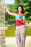 Student girl reading book in front lake Royalty Free Stock Photo