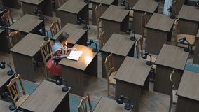 The Reading Hall. Student girl reading book in a library hall with tables and lamps, top view of indoor room stock footage