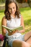 Student girl reading book in park summer Stock Photography