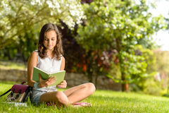 Student girl reading book sitting on grass Royalty Free Stock Images