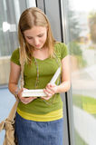 Student girl reading book standing by window Stock Photos