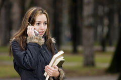 Student girl received happy ne. A student girl received happy news by mobile phone Stock Photography