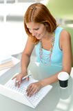 Student girl sitting behind modern desk laptop Royalty Free Stock Photos