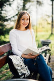 The student girl sitting on a bench, reading a book Royalty Free Stock Image