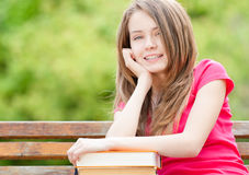 Student girl sitting on bench and smiling. Beautiful and happy young student girl sitting on bench, her hands on pile of books, looking into the camera and Stock Image