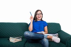 Student girl sitting on couch holding pen like good idea. With books around isolated on white background royalty free stock photo