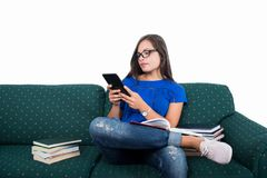 Student girl sitting on couch holding tablet with books around. Isolated on white background royalty free stock photos