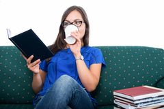 Student girl sitting on couch reading drinking coffee stock images