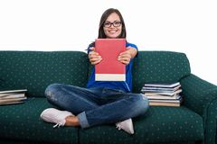 Student girl sitting on couch showing notebook. With books around and smiling isolated on white background stock photography