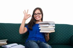 Student girl sitting on couch showing ok holding books stock photo