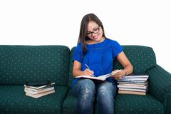 Student girl sitting on couch studying with books around. Isolated on white background stock images