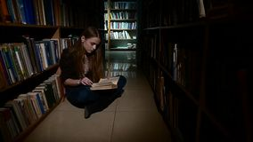 Student girl sitting on floor and examines book in stock video