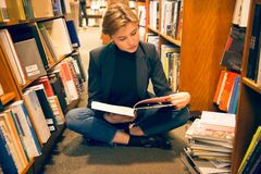 Student girl sitting on the floor and reading a book in the library Royalty Free Stock Photo