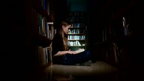 Student girl sitting on floor and reading book in stock video footage