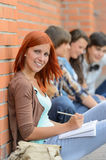 Student girl sitting outside campus with friends Stock Photo