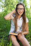 Student girl sitting in park with book Royalty Free Stock Images