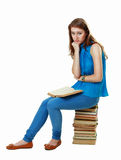 Student girl sitting on pile of books Royalty Free Stock Image