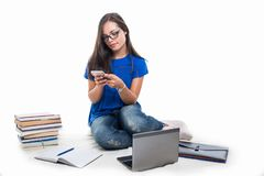 Student girl sitting texting on smartphone Royalty Free Stock Image