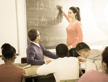 Student girl solves task near blackboard in classroom mathematic Royalty Free Stock Photo
