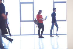 Student girl standing with laptop, people group passing by Stock Photography