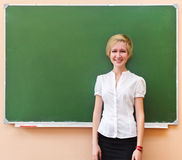 Student girl standing near blackboard in the classroom Royalty Free Stock Image