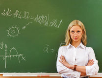 Student girl standing near blackboard in the classroom Royalty Free Stock Photos