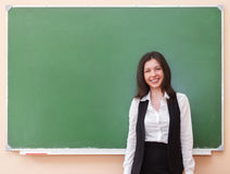 Student girl standing near clean blackboard Royalty Free Stock Photos
