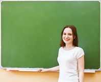 Student girl standing near clean blackboard in the classroom Royalty Free Stock Image