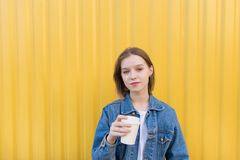 Student girl stands with a cup of coffee in her hands on a yellow background and looks at the camera royalty free stock photos