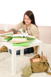 Student girl studying home sitting on floor Stock Image