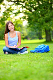 Student girl studying in park going back to school. At university college. Happy student sitting studying, writing and reading outside. Multi ethnic Chinese Stock Images