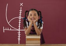 Student girl at table against red blackboard with education and school graphic Stock Image