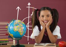 Student girl at table against red blackboard with school and education graphic Royalty Free Stock Images