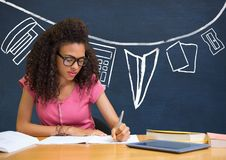 Student girl at table writing against blue blackboard with school and education graphic Royalty Free Stock Images