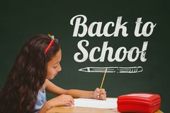 Student girl at table writing against green blackboard with back to school text Stock Photos