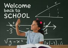 Student girl at table writing against green blackboard with welcome to school text Royalty Free Stock Images