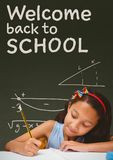 Student girl at table writing against green blackboard with welcome to school text Royalty Free Stock Photo