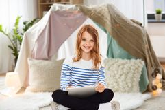 Student girl with tablet pc at home. Technology, people and internet concept - little student girl with tablet pc at home over kids room and tepee background Royalty Free Stock Photos