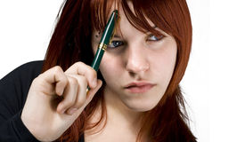 Student girl thinking about a dilemma. Cute girl with red hair holding a pen against her forehead and thinking. Studio shot stock photo