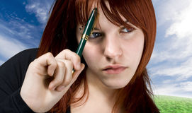 Student girl thinking about a dilemma. Cute girl with red hair holding a pen against her forehead and thinking. Studio shot stock photos