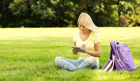 Student girl with touchpad and backpack in park Royalty Free Stock Images
