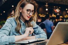 Student girl in trendy glasses sits in cafe in front of computer, laptop watches educational webinar. Online education. A student girl in trendy glasses sits in royalty free stock image