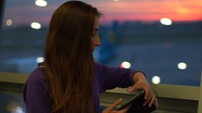 A student girl uses a smartphone, standing at the airport waiting for her flight stock footage