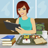 Student girl using tablet sitting in fast food restaurant Royalty Free Stock Images